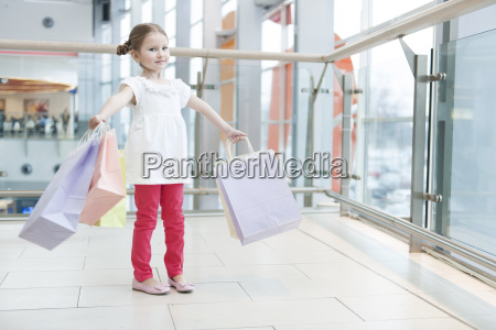 young girl laden with paper shopping