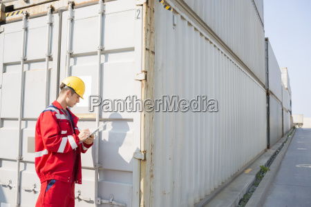 male worker inspecting cargo container while