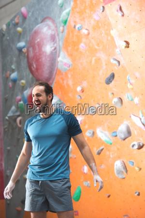 dedicated man shouting by climbing wall