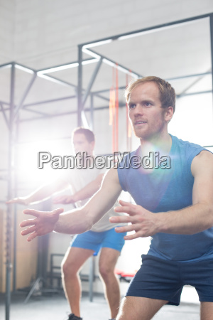 determined men exercising at crossfit gym