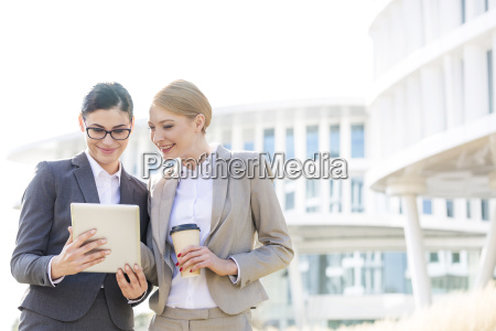 happy businesswomen using digital tablet outside