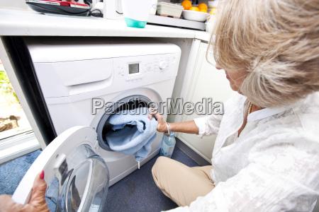 senior woman loading towel in washing