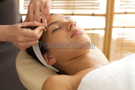 young woman having eye brows plucked