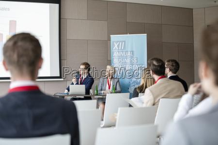 businessman giving presentation in seminar hall