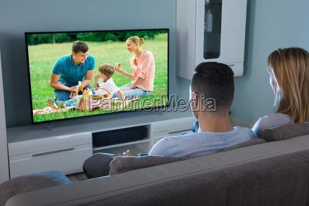 couple watching video on television