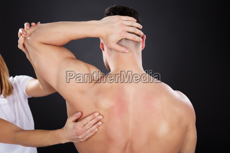 physiotherapist giving shoulder massage