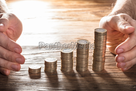 man protecting his coin stacks on