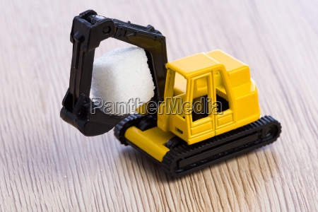small yellow toy excavator grabbing a