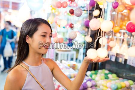 woman, choosing, lantern, in, street, market - 21585373