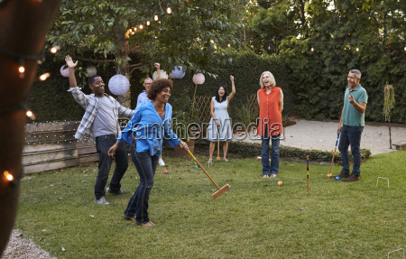 group of mature friends playing croquet