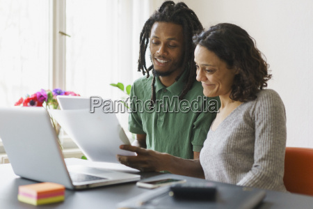 couple reading documents while sitting with