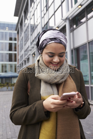 british muslim woman texting on mobile