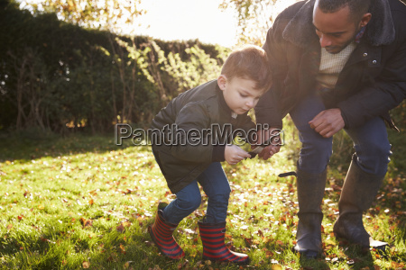 boy and father playing with feather