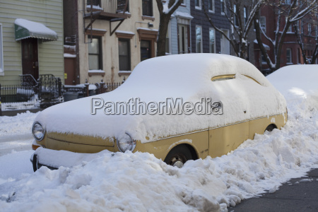 snow covered car on street in