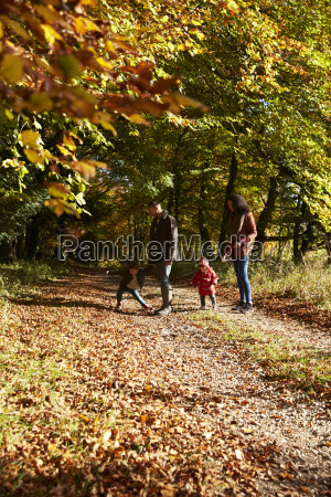 family on autumn walk in woodland