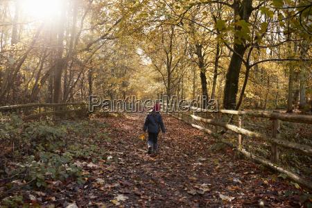 young girl walking along path through