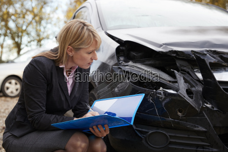female loss adjuster writing report on