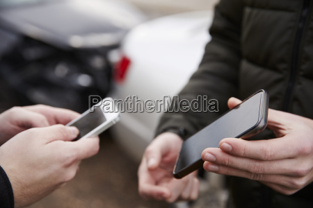 two drivers exchanging insurance details after
