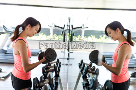 sport woman practices weight lifting of