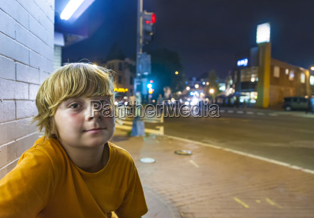 cute boy smiles tired while sitting