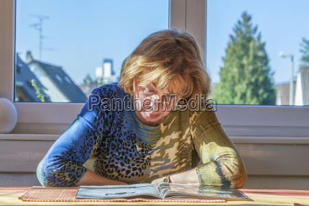 elderly attractive woman reading in a