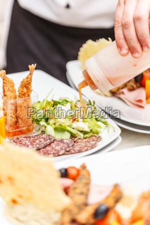 chef is garnishing appetizer dish