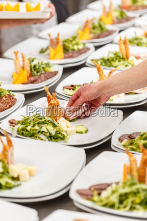 cook is garnishing appetizer plates
