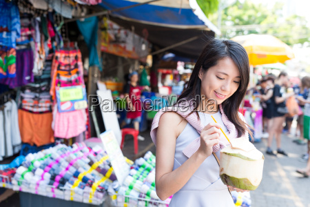 woman enjoy coconut juicy at street