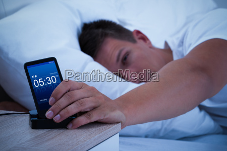 man waking up with mobile alarm