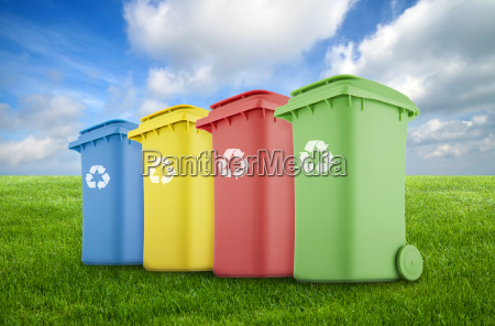 four colorful recycle bins on green