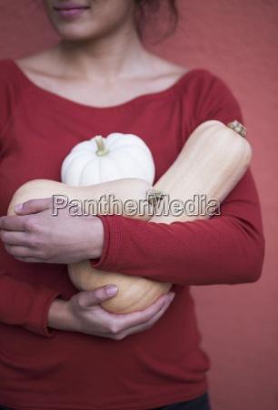 a woman holding different pumpkins