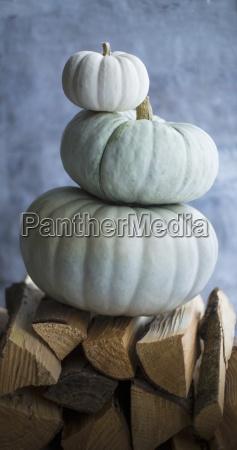 three pumpkins stacked on firewood