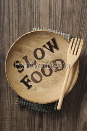 slow food written on a wooden