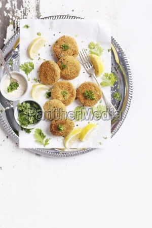 fish burgers with lemon wedges and