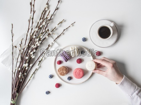 a hand taking macarons from a