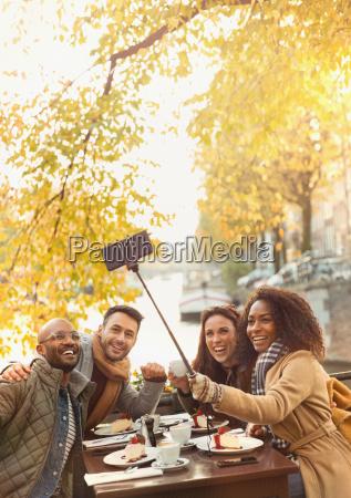 smiling friends taking selfie with selfie