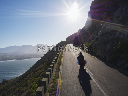 couple riding motorcycle on sunny road