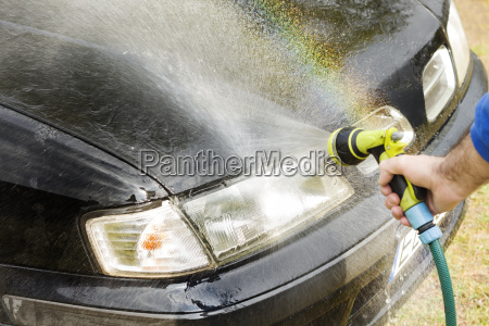 washing the car man rinses the