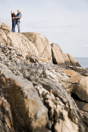 mature couple hugging on rocks