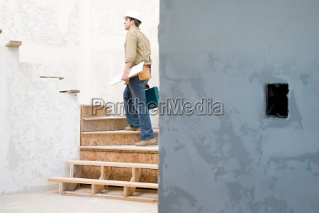 a builder walking up stairs
