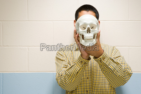 male student holding a human skull