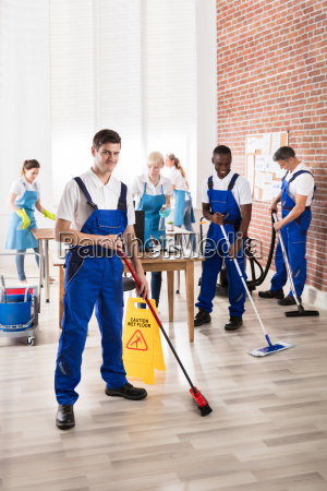diverse janitors cleaning the office