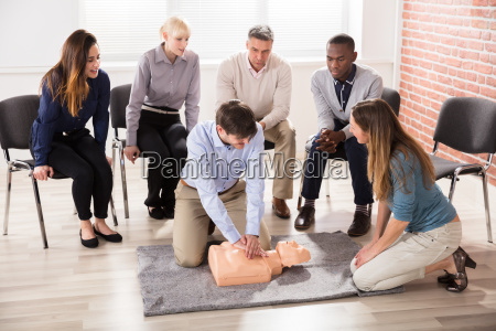 first aid instructor showing cpr training