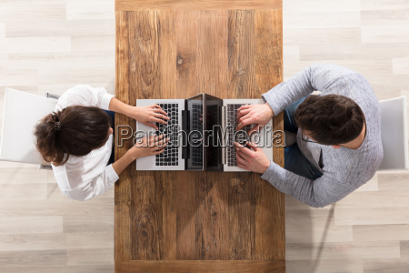 overhead view of couple using laptop