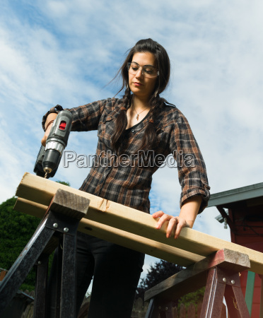 craftsperson woman uses power screwdriver drilling