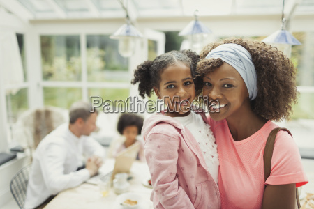 portrait smiling mother and daughter hugging