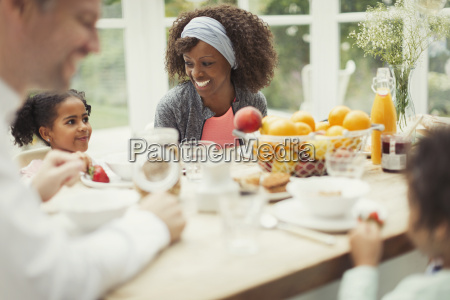 multi ethnic young family eating breakfast