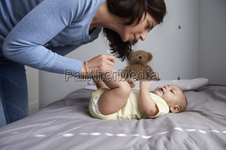 mother playing with newborn baby son