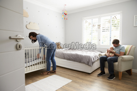mother making up bed in nursery