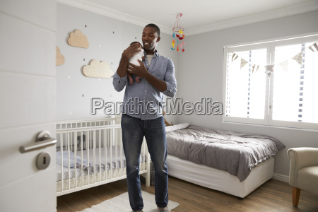 father holding newborn baby son in